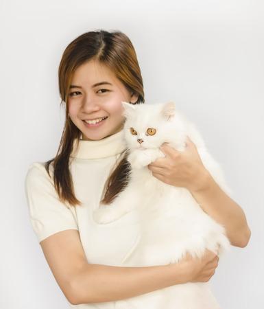 Beautiful Asian teen holding a  white cat. photo