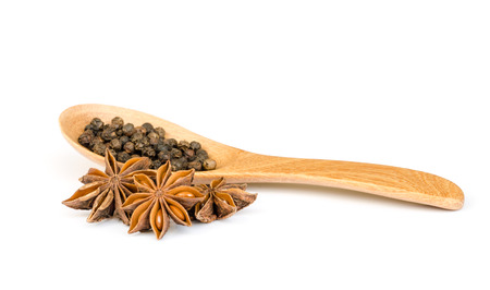 piperine: peppercorn and wood spoon  on white background .
