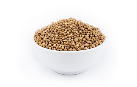 Pile of coriander seeds isolated on white background .