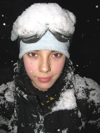 Young woman wearing a ski mask and covered with snow.