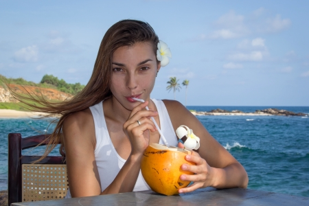 hot water: Young girl with coconut on the see side