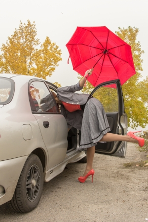 Happy woman outdoor in autamn with red umbrella near the car