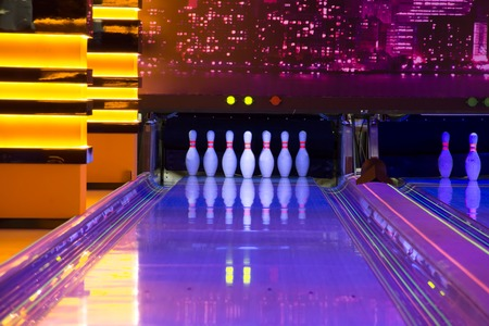 Pins at the end of a bowling alley of glow in the dark bowling
