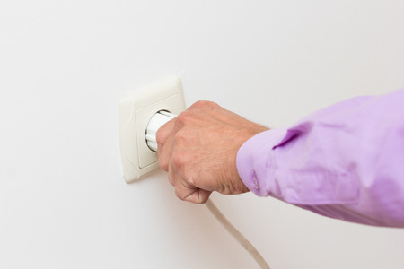 unplugging: Close Up Of Hand Putting Plug Into Electricity Socket.