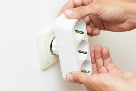 unplugging: Hands inserting electrical tee adapter into the socket Stock Photo