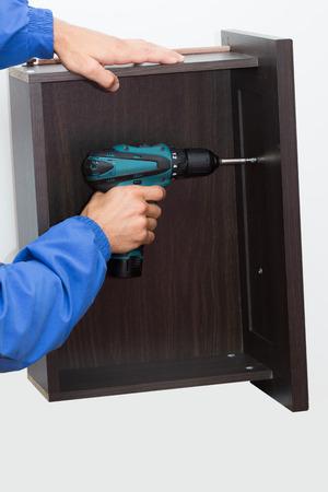 furniture hardware: Manos con destornillador montaje elemento de mobiliario