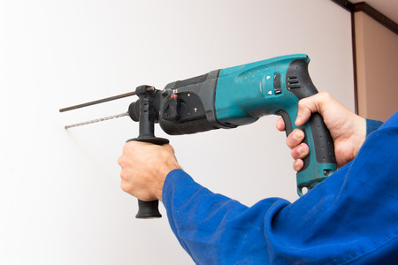 perforator: Construction worker is boring the wall by electric perforator
