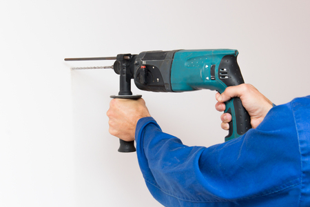 mounter: Construction worker is boring the wall by electric perforator