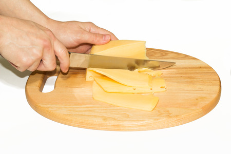womans: Close up of womans hands cutting hard cheese with knife on cheese board isolated on white Stock Photo