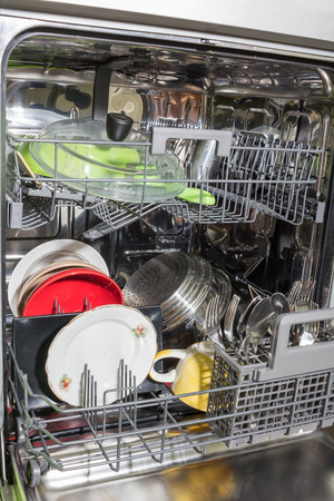 dishwasher: Opened dishwasher with clean dishes.