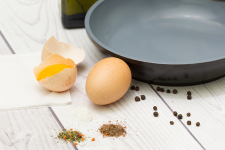 Preparing homemade dietary supplements. Pan on a white wooden table. Eggs, oil, pan, spices