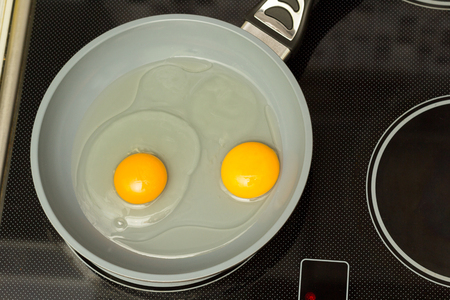 Frying pan with two raw eggs and oil