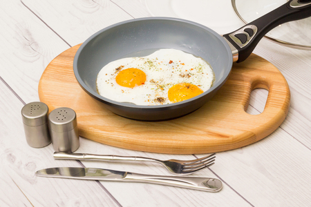 Frying pan with cooked two eggs and spices Stock Photo