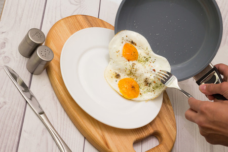 Frying pan and plate with cooked two eggs and spices