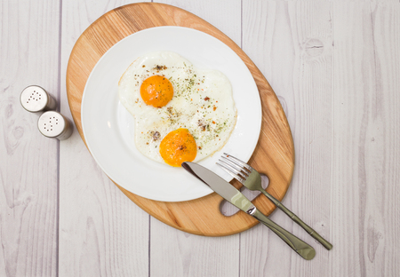 Plate with cooked two eggs and spices Stock Photo