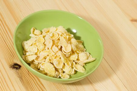 A bowl of Corn flakes on wooden table Stock Photo