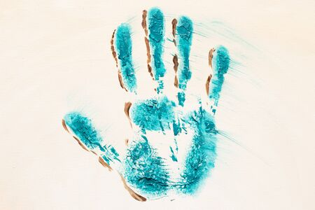 Oil painted turquoise handprint on white canvas background