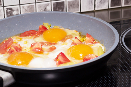 Fried eggs with vegetables in a frying pan on the electrical stove