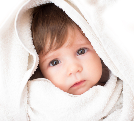 Sad baby girl in white towel after shower