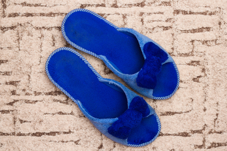 Blue slippers on carpet. Welcome home concept. Stock Photo