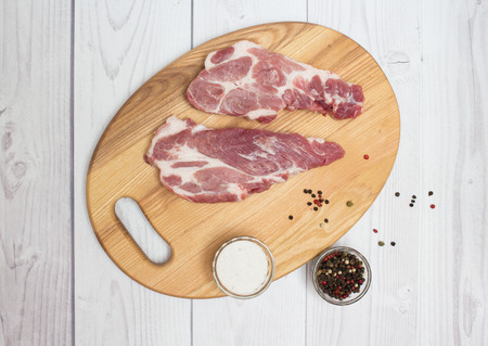 plump: Two raw plump  pork neck chops with spices on wooden cutting board