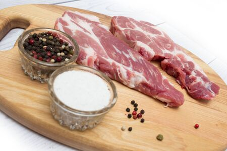 Two raw plump  pork neck chops with spices on wooden cutting board