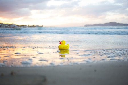 Yellow small toy duckling on sand beach in evening. Crete, Greece.