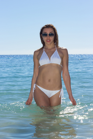 Beautiful luxury slim girl in a white bikini on the beach. Outdoor summer lifestyle image of young pretty woman outfit and sunglasses, fun ,joy, emotions. Stock Photo