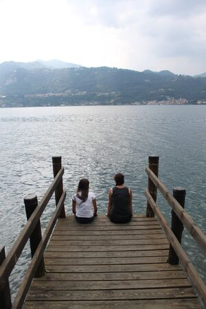 girls sitting, Wooden pier Lake Orta piedmont Italy photo