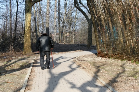 The old man of Italy stands in a park with a walking stick photo
