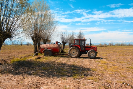 Tractor on a dirt path in autumn, the farmer is working on the fields photo