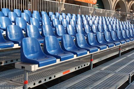 sports venue:  Blue plastic old stadium seats on concrete steps