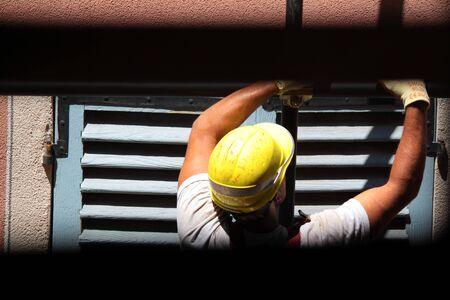 worker man at work above exterior house roof packaging Reklamní fotografie