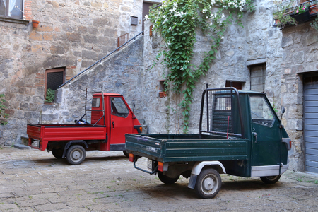 lazio: BOLSENA, ITALY - JUNE 28, 2015:picturesque old street with dwellings and an ancient italian vehicle Ape Piaggio in the Bolsena, Lazio.