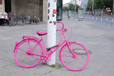 padlocked: Pink bicycle padlocked to post in Berlin, Germany, Europe Stock Photo