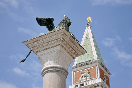 VENICE, ITALY - MAY 8, 2010: Two symbols of Venice: the Lion, the San Marco bell tower. Banque d'images - 104795865