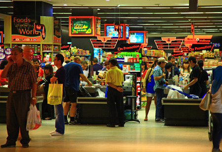 KUALA LUMPUR, MALAYSIA - 21 JANUARY, 2014: Supermarket customers paying their shopping to cashiers. 新聞圖片