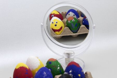 Spiegelbeeld van geschilderde Pasen-egghead in een lijstspiegel