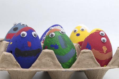Beschilderde eieren met gezichten in eierdoos Stockfoto