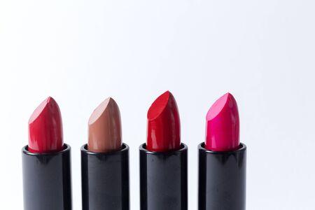 Vier verschillende gekleurde lippenstiften tegen witte achtergrond