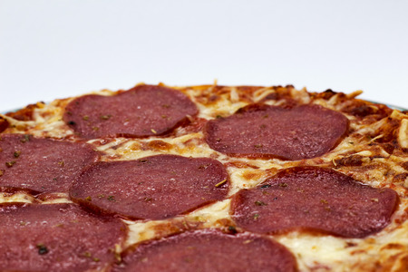 Salamipizza tegen witte achtergrond