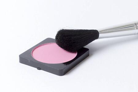 Roze rouge blusher met borstels tegen witte achtergrond