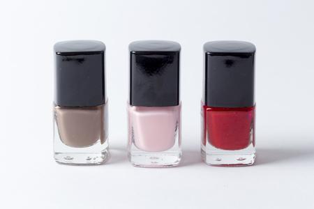 3 verschillende gekleurde nagellakflessen tegen witte achtergrond Stockfoto