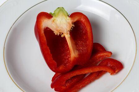 Gesneden ?? paprika's op witte plaat tegen witte achtergrond Stockfoto