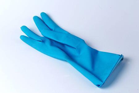 Blauwe rubberhandschoenen tegen witte achtergrond Stockfoto