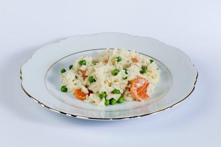 Rice plantaardige pan op een witte plaat tegen een witte achtergrond