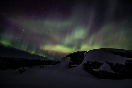 Northern lights aurora borealis seen from the rocky peak of Mount Aurora near Fairbanks, Alaska