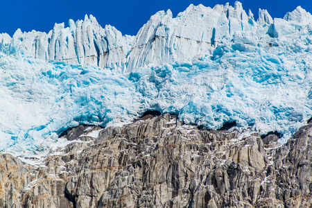 Massive walls of ice tower above a rock cliff on the edge of the Harding icefield on the Kenai Peninsula, Alaska
