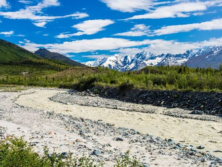 Milky brown water tumbles into the taiga from the high glaciated mountains