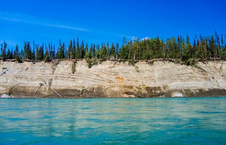 The emerald glacial waters of the Kenai River, Alaska cut a deep bank here